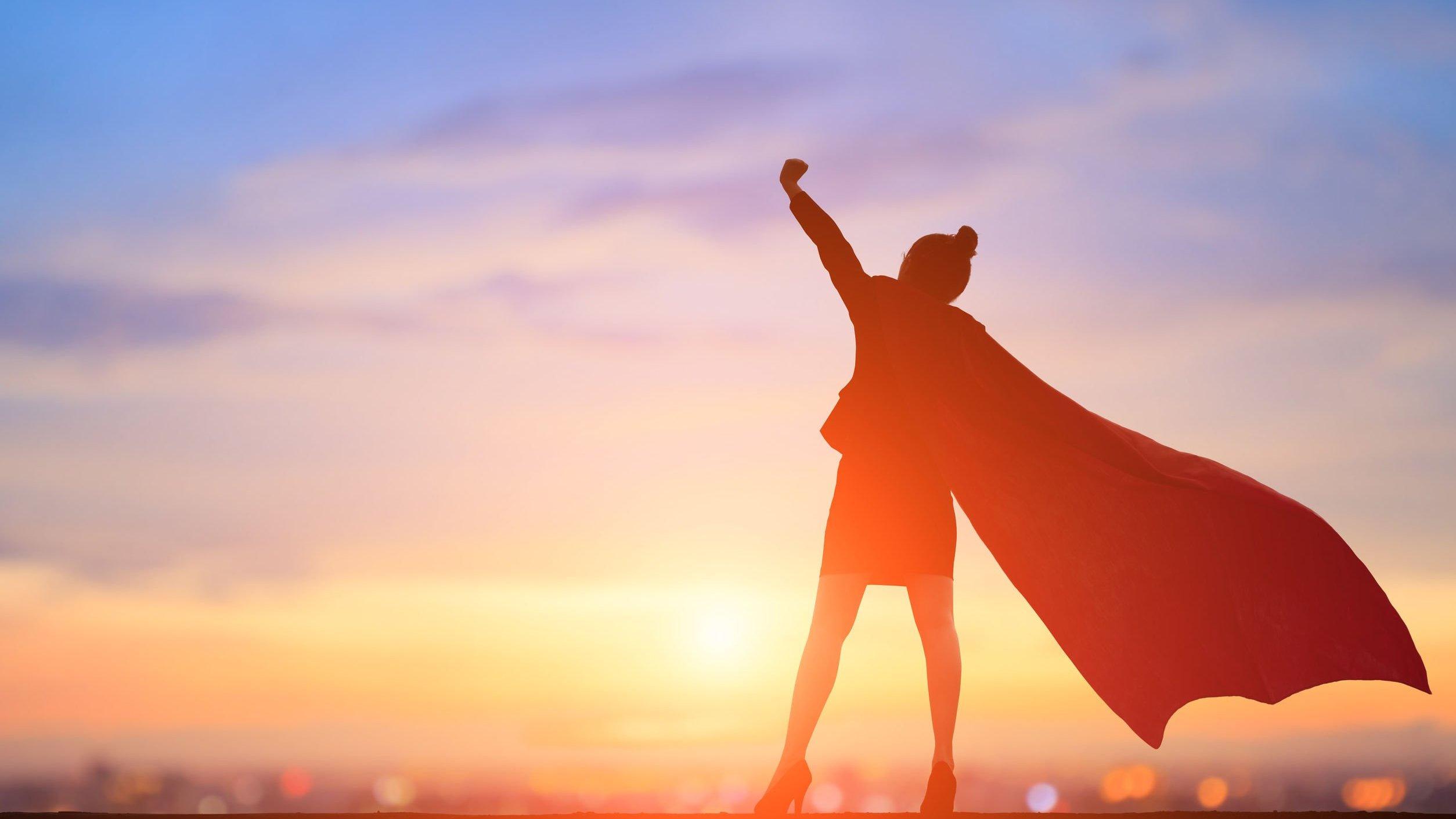 Mulher vestida com uma capa de heroína enquanto ergue um braço direcionado ao céu.
