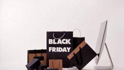 Sacolas de papel pretas e marrons em frente a um computador branco.