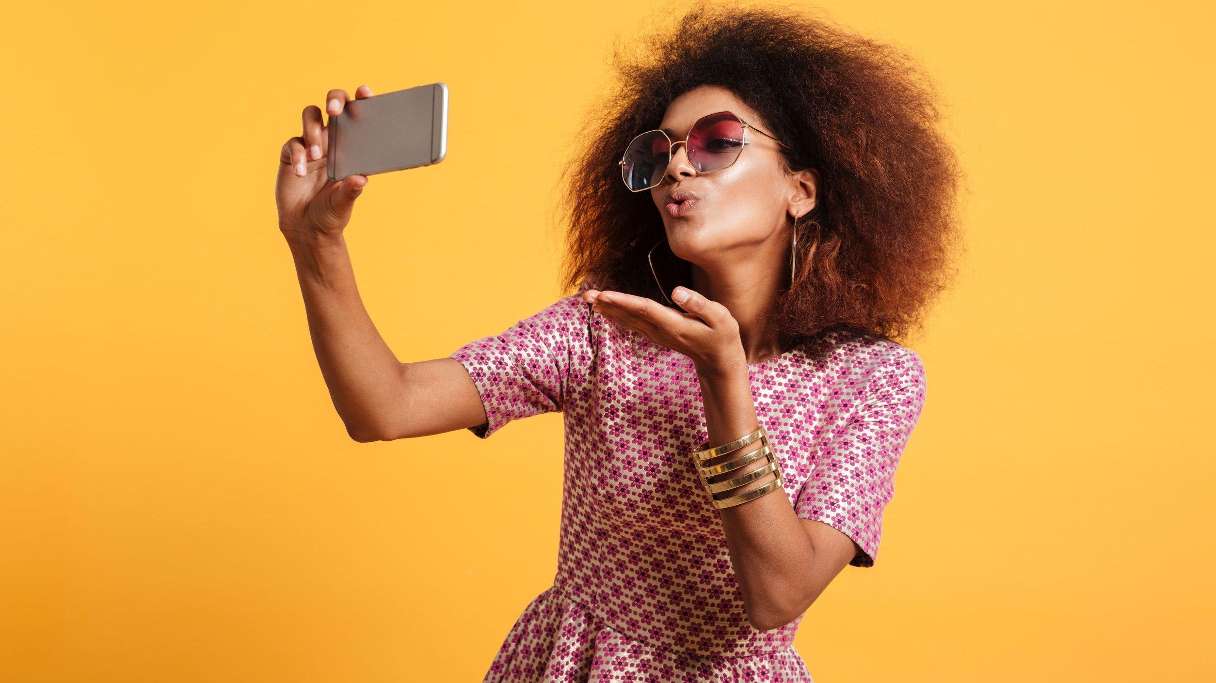 Mulher fotografando a si mesma em um cenário amarelo.