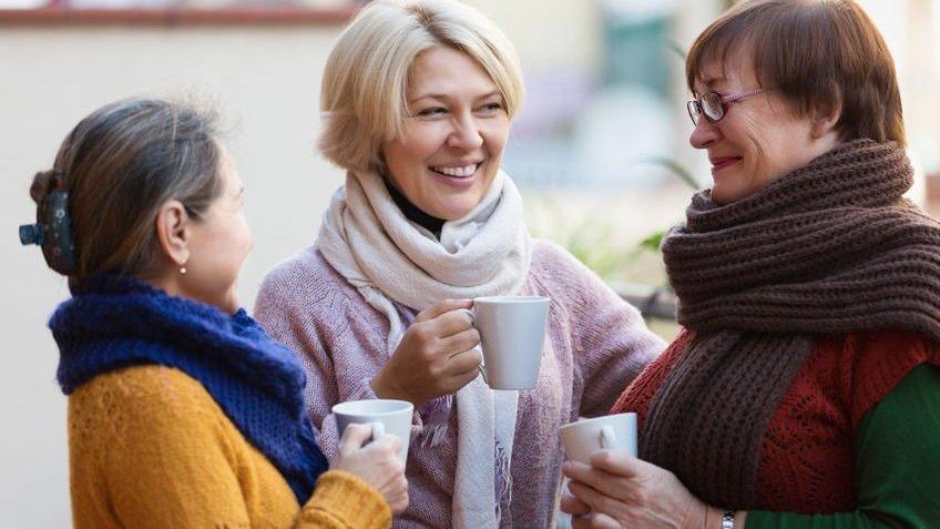 Três amigas de longa data conversam enquanto tomam um café