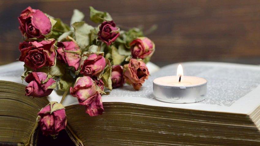 Uma vela e rosas secas em cima de uma bíblia