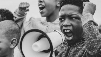 Menino negro gritando no megafone em protesto
