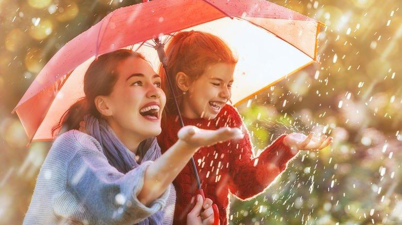 Menina de blusa vermelha e sua mãe felizes embaixo de um guarda-chuva enquanto chove