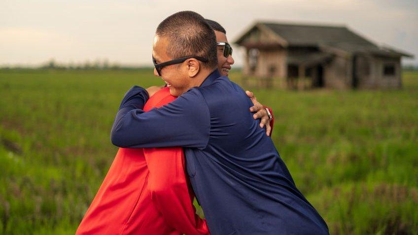 Dois amigos se abraçam, sorrindo.  Ao fundo, um gramado e uma pequena casa de madeira.