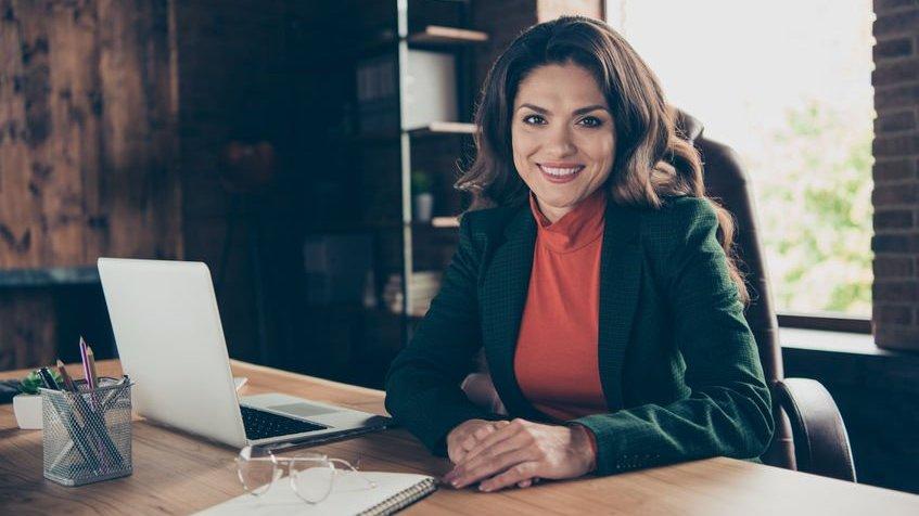 Mulher morena sorrindo sentada em frente uma mesa com computador aberto em um escritório