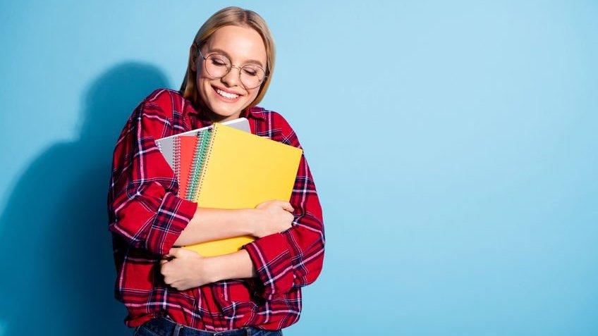 Garota loira de óculos usando blusa xadrez abraçando vários cadernos.