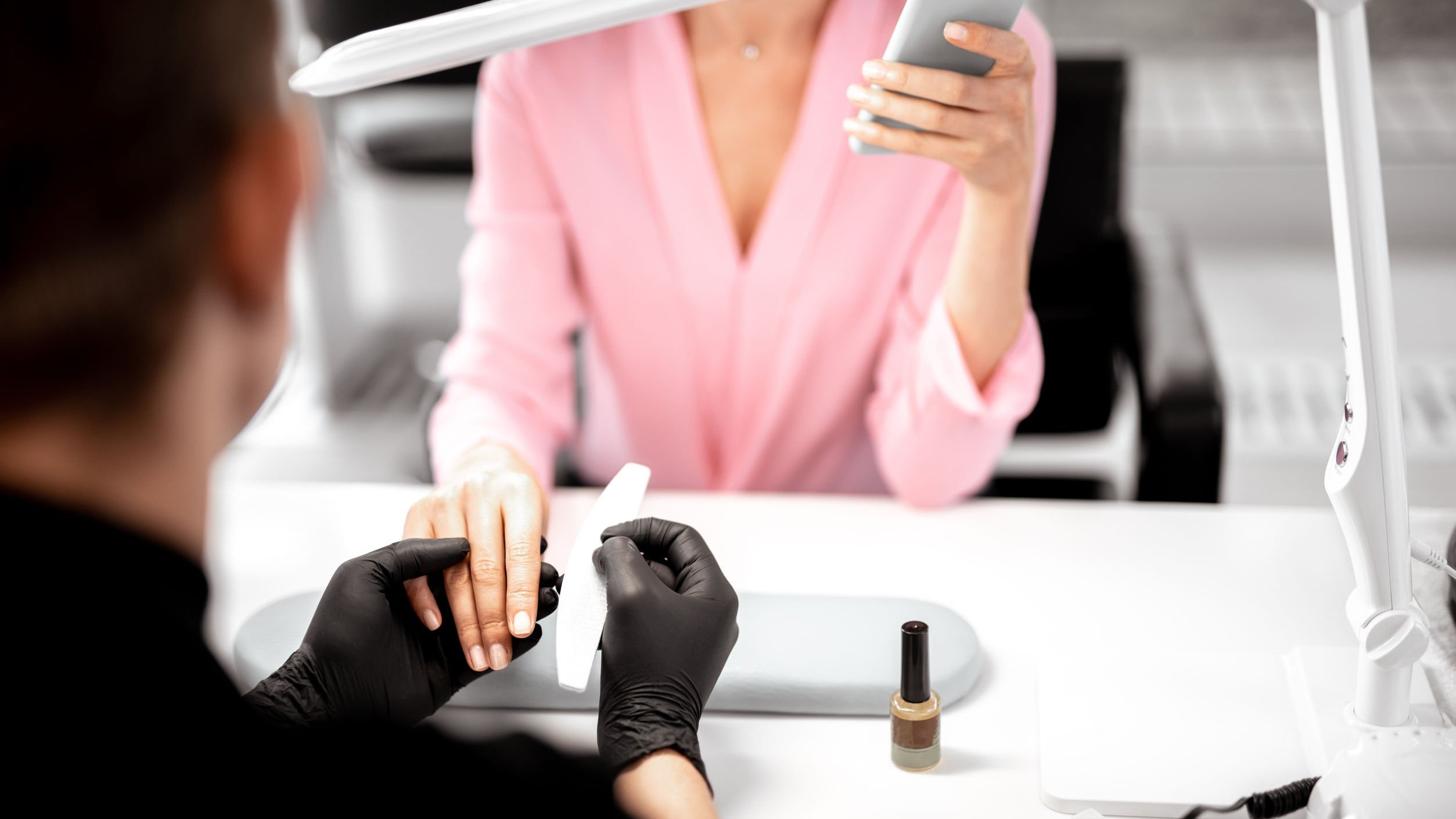 Manicure fazendo unha de mulher.