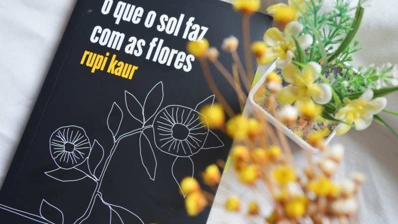 Livro O que o Sol faz com as flore sobre mesa branca, ao lado de arranjo de flores amarelas