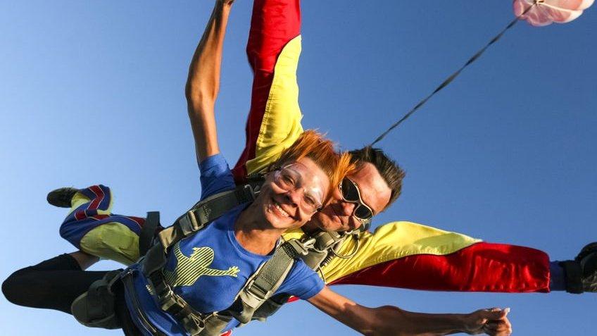 Mulher com o instrutor saltando de paraquedas