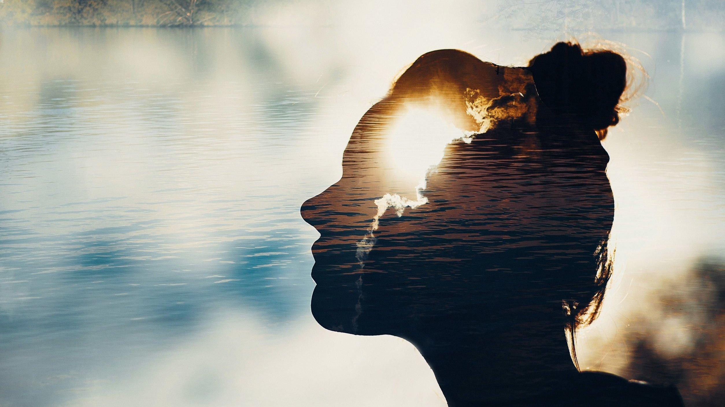 Silhueta de uma mulher com paisagem em segundo plano