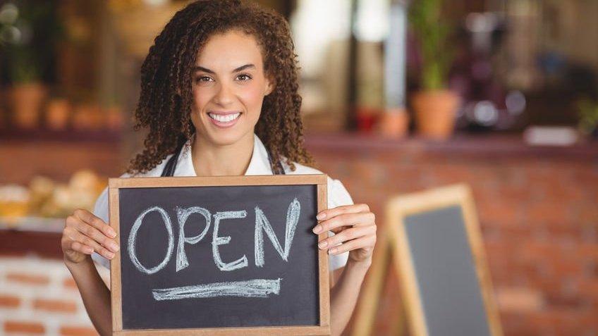 Mulher segurando um quadro escrito open (aberto, em inglês)