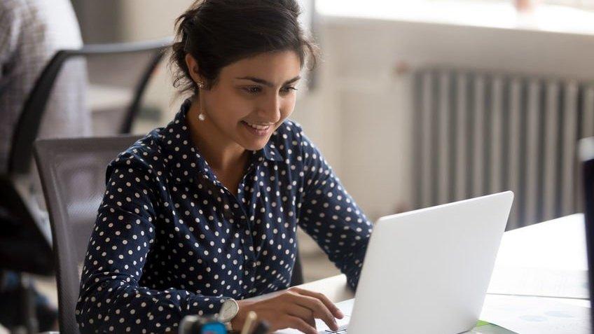 Mulher de cabelo amarrado usando camisa e sorrindo enquanto mexe no computador