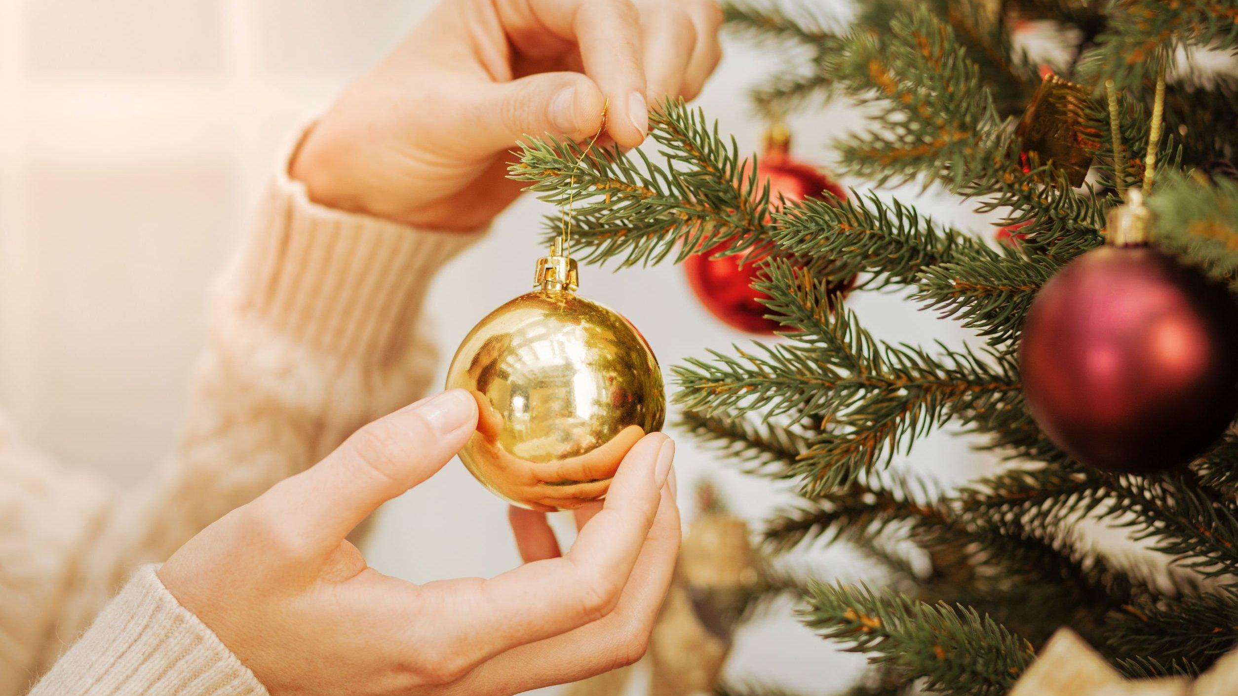 Mulher colocando enfeite de natal na árvore
