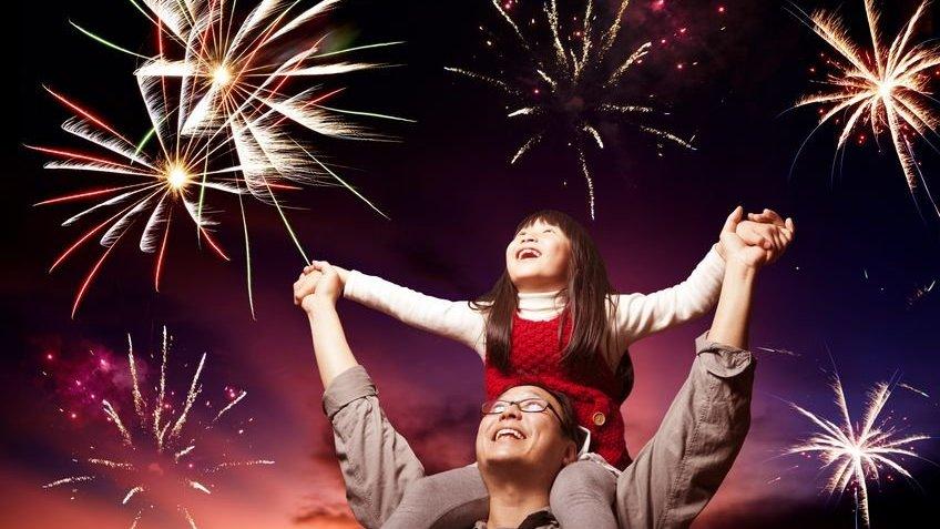 pai e filha olhando fogos de artifício no céu