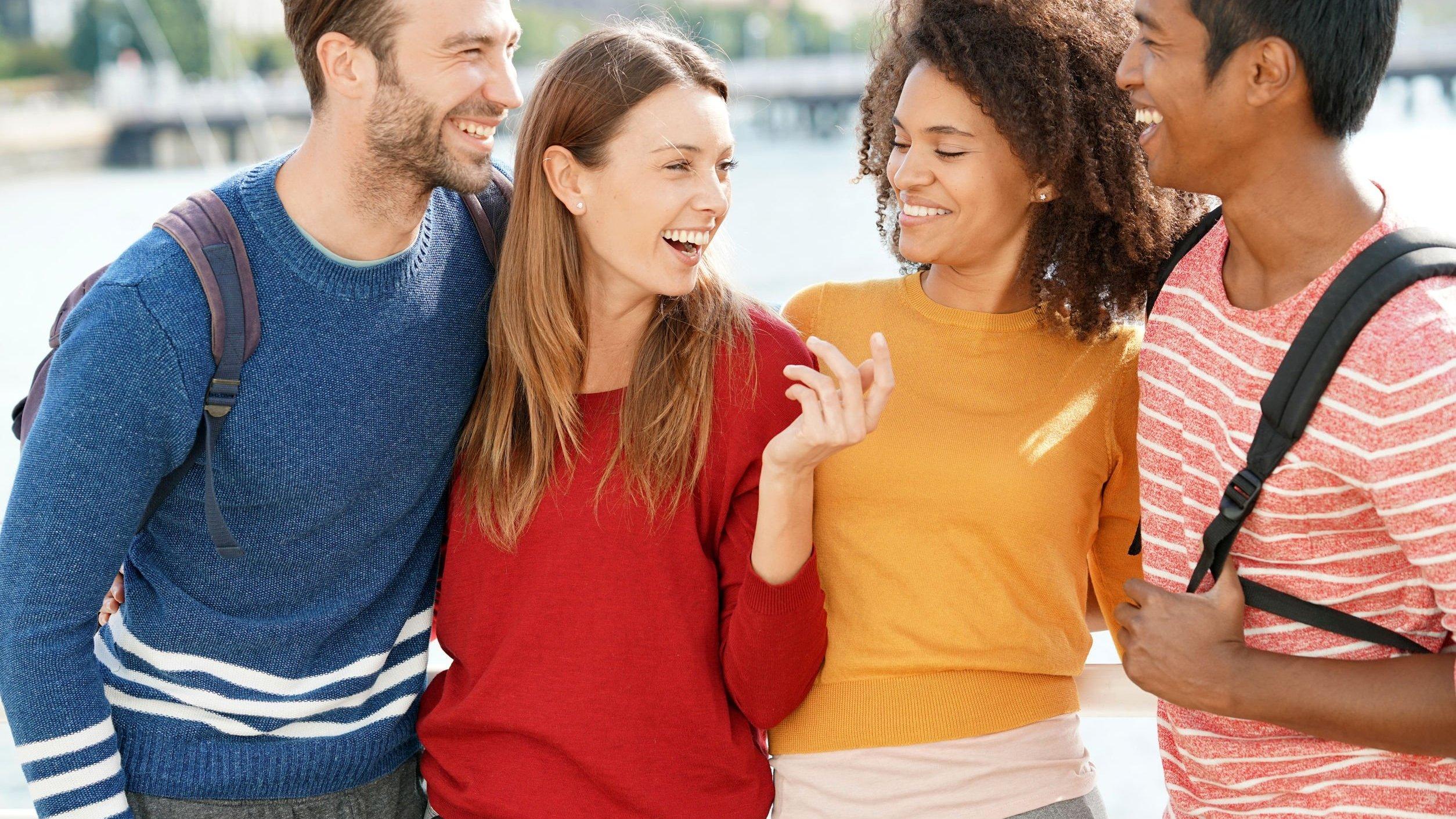 Grupo de amigos sorrindo, conversando.