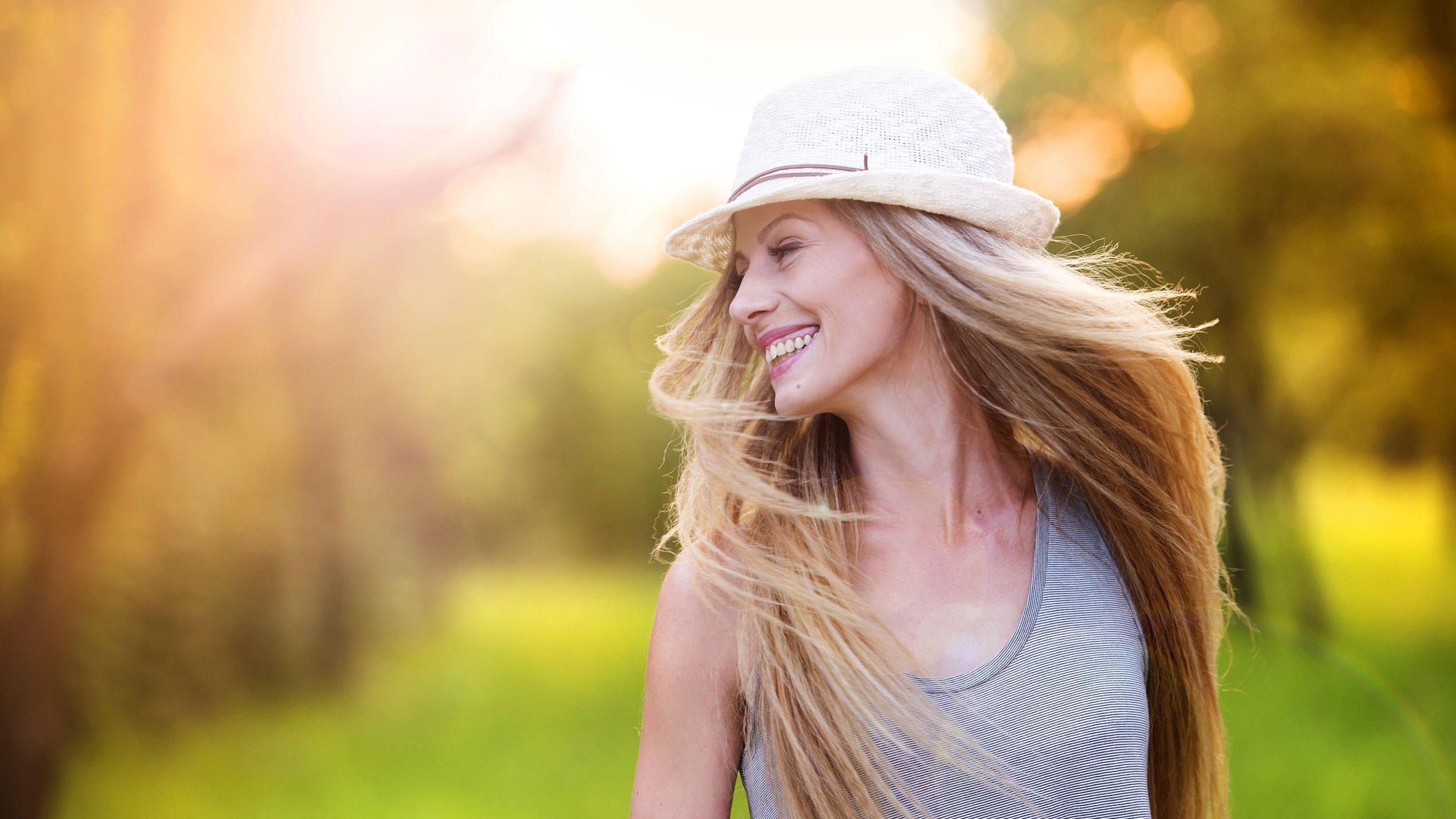 Mulher de chapéu sorri. O cenário é de árvores e grama