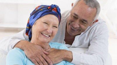 Mulher com lenço na cabeça sendo abraçado por um homem
