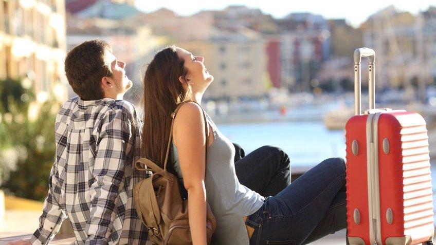 Casal  com uma mala sentados na calçada relaxando