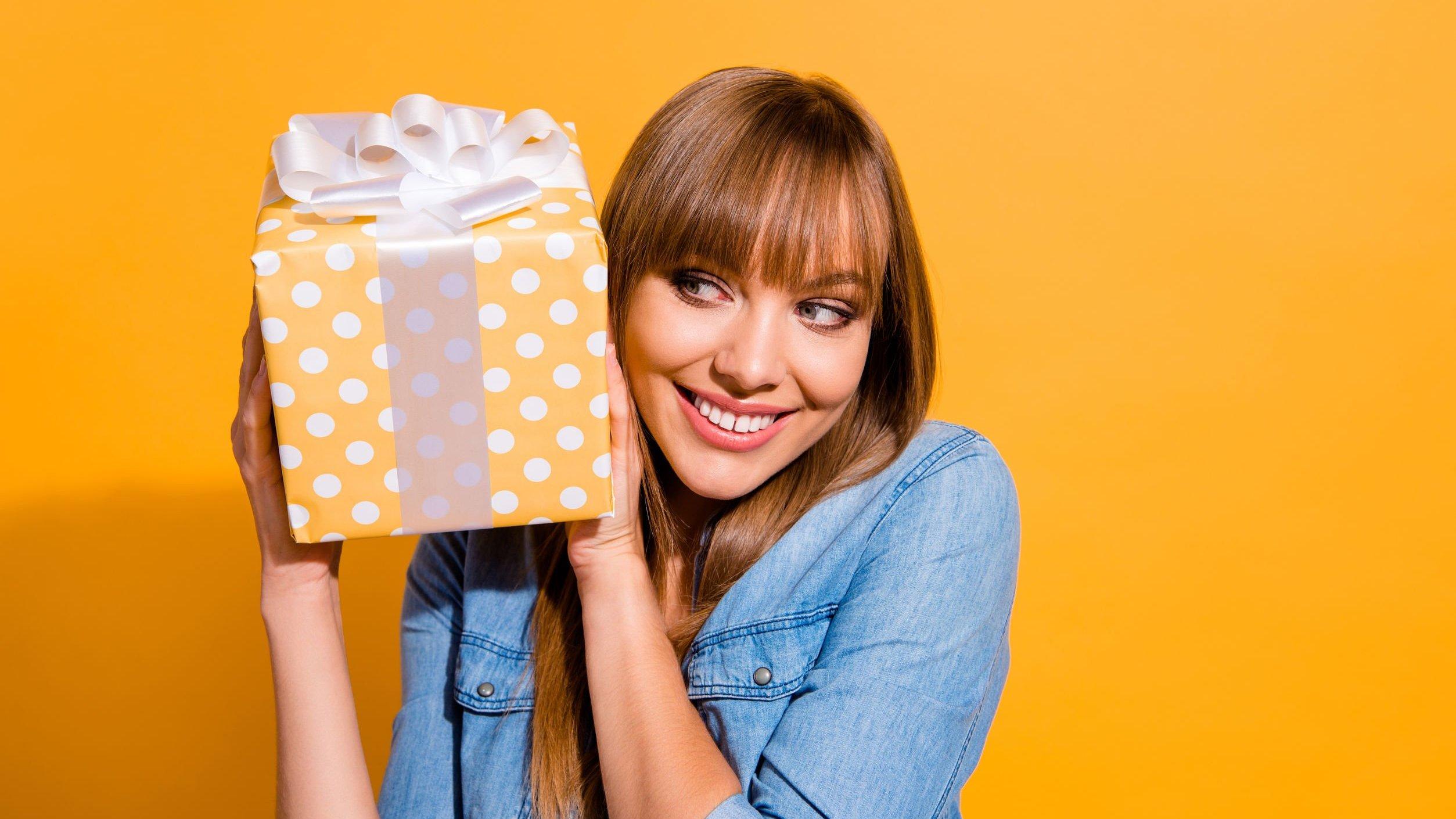 Mulher sorridente segurando caixa de presente.