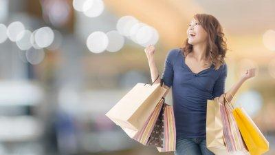 Mulher sorridente com sacolas de compras em ambos os braços