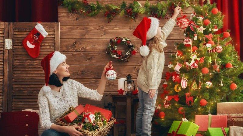 Mãe e filha decoram a árvore de Natal na sala.