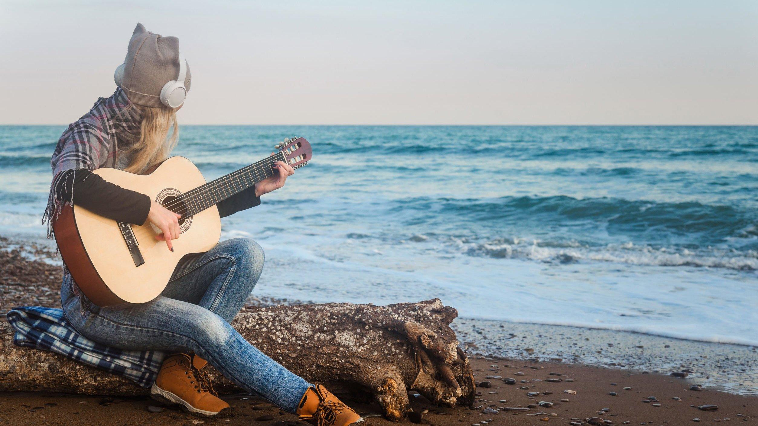 Mulher tocando violão, de frente pro mar.