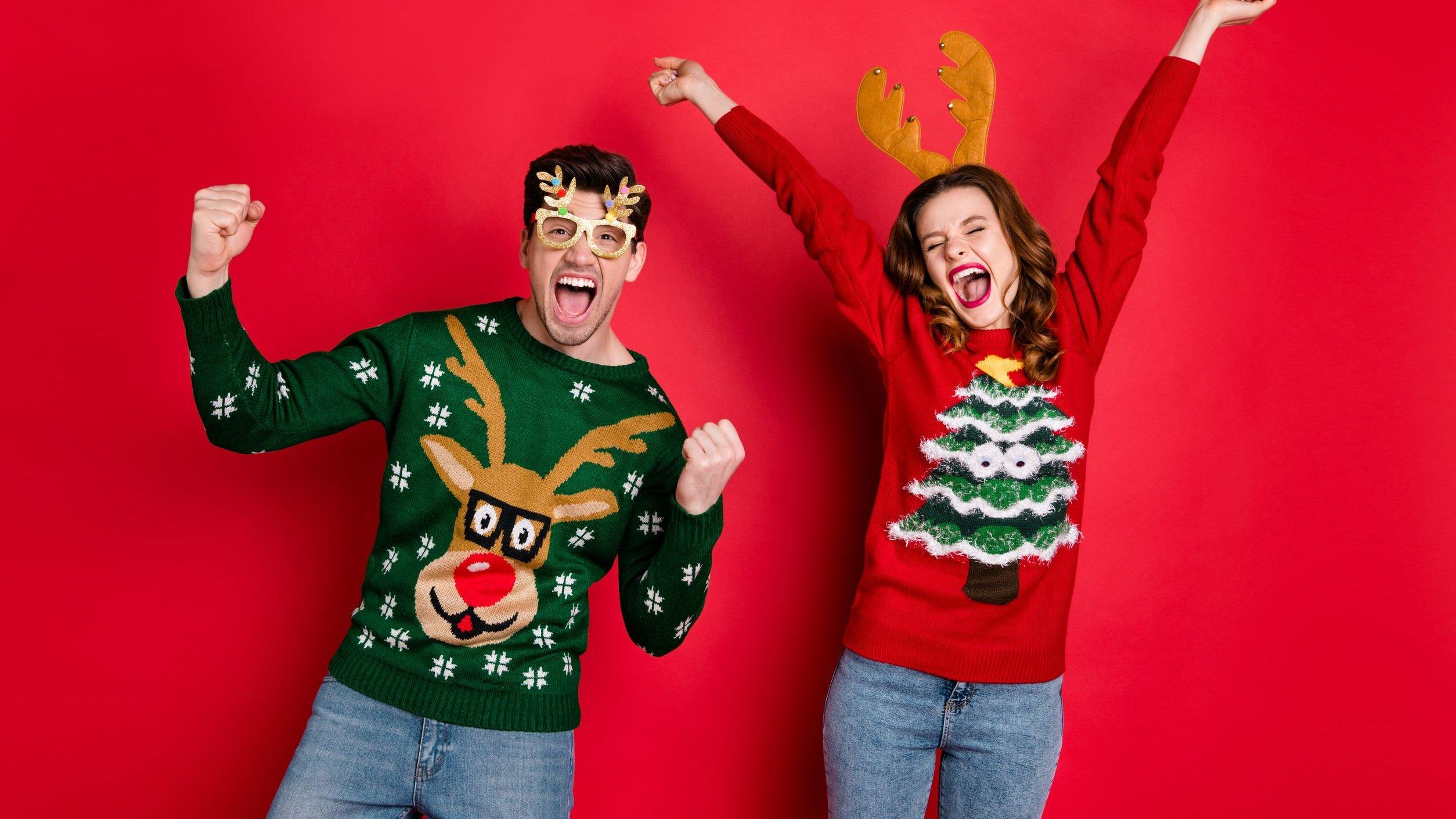 Homem e mulher vestidos com roupas de Natal, comemorando.