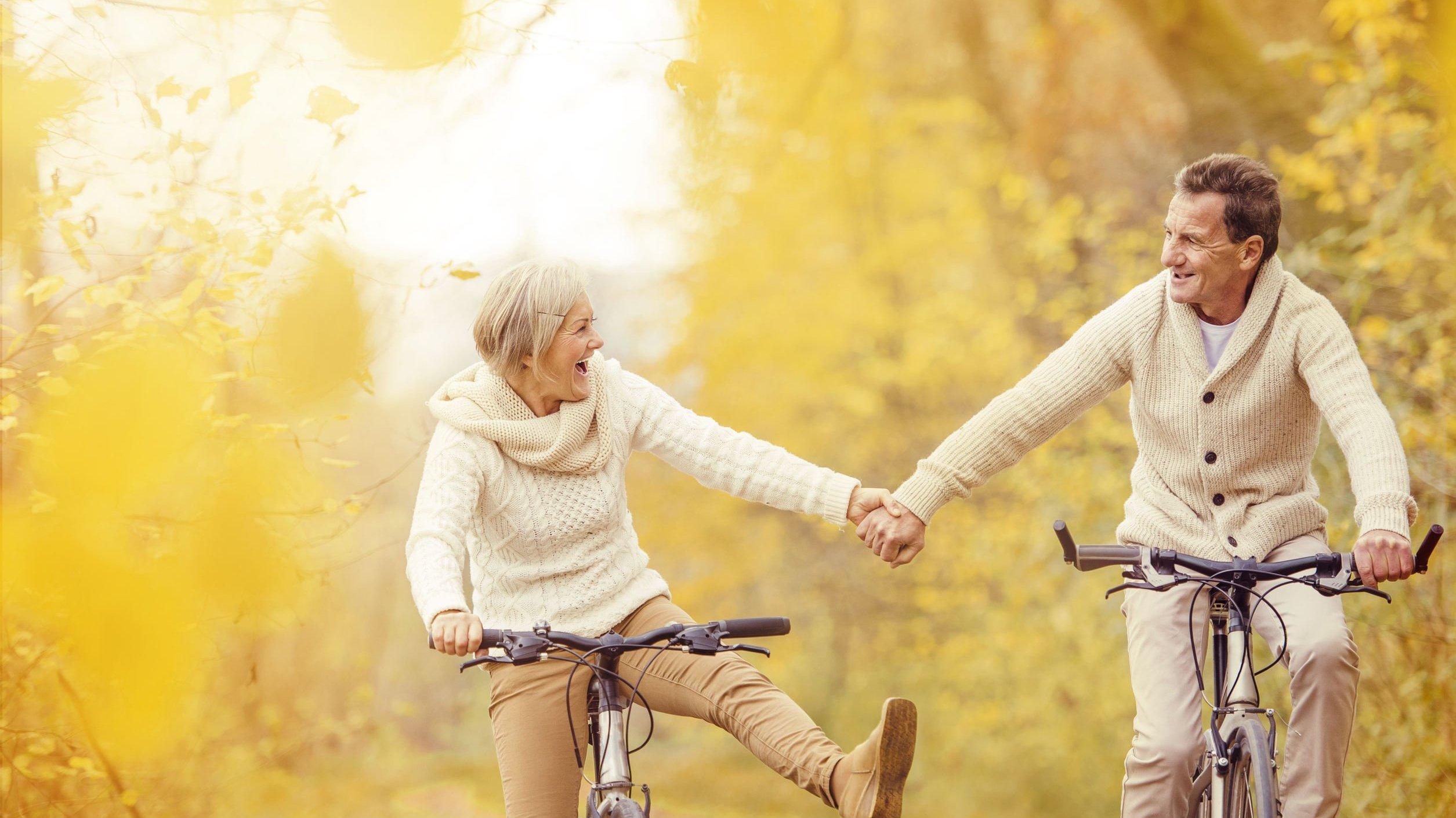 Casal de idosos andando de bicicleta em parque, com  as mãos dadas.