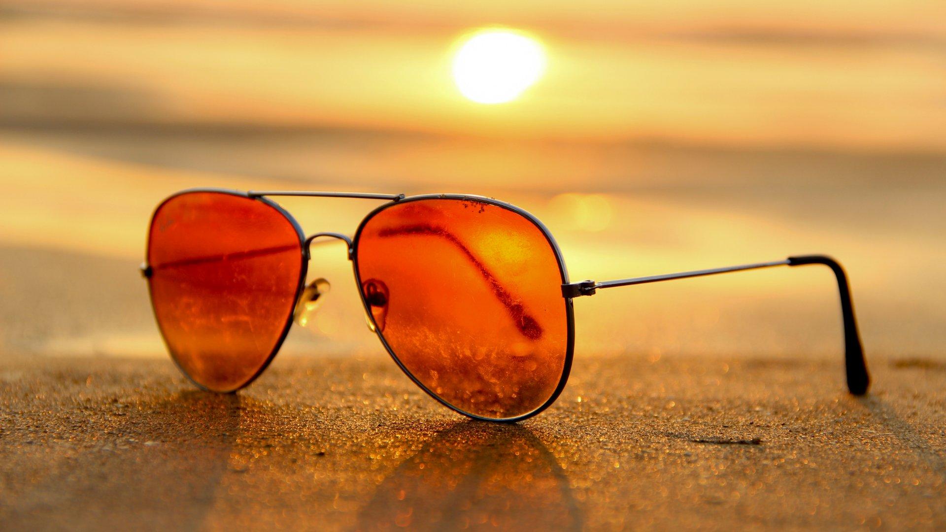 Foto de um óculos escuro com o pôr do sol ao fundo