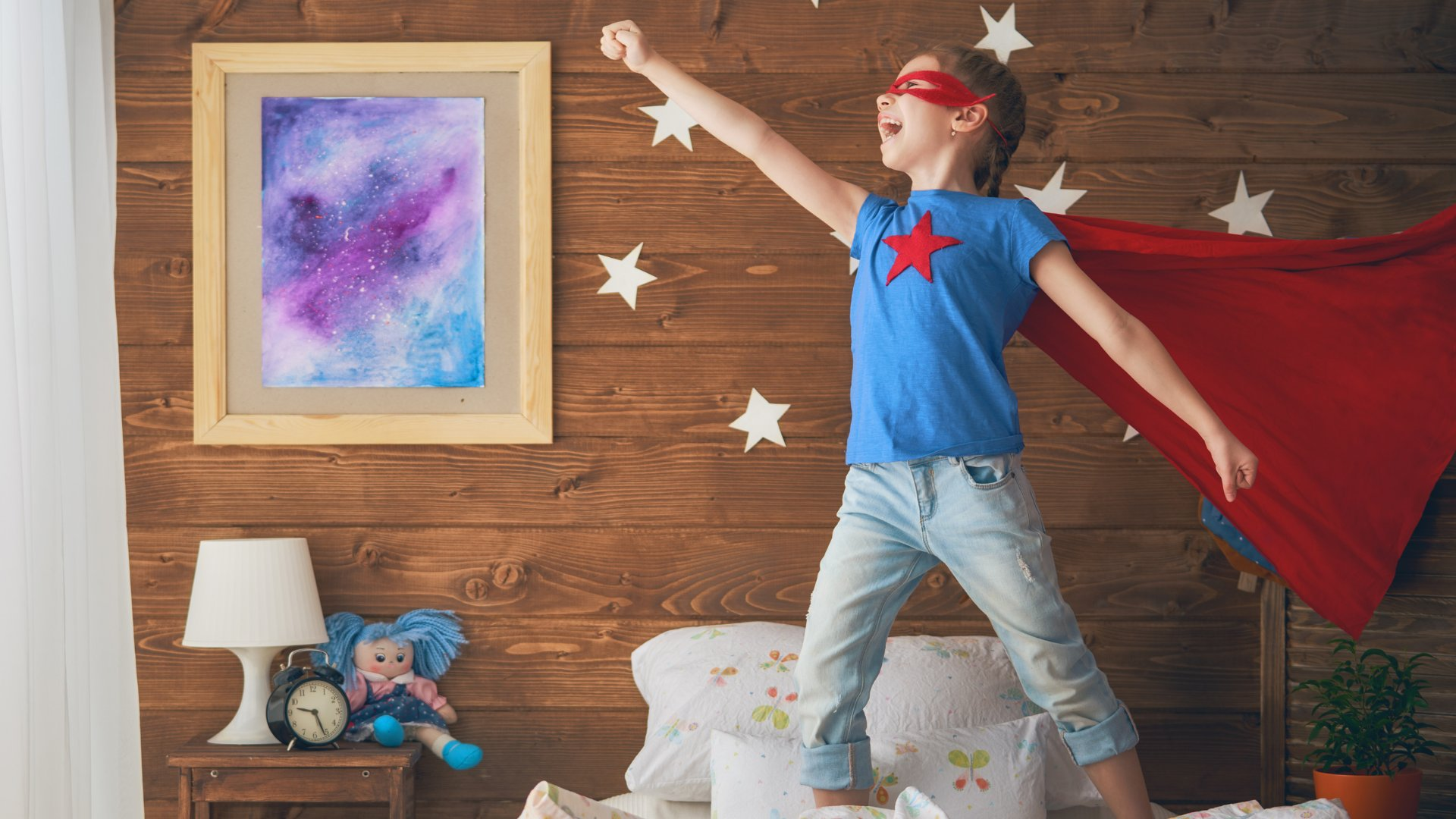 Criança brincando de super-herói no quarto