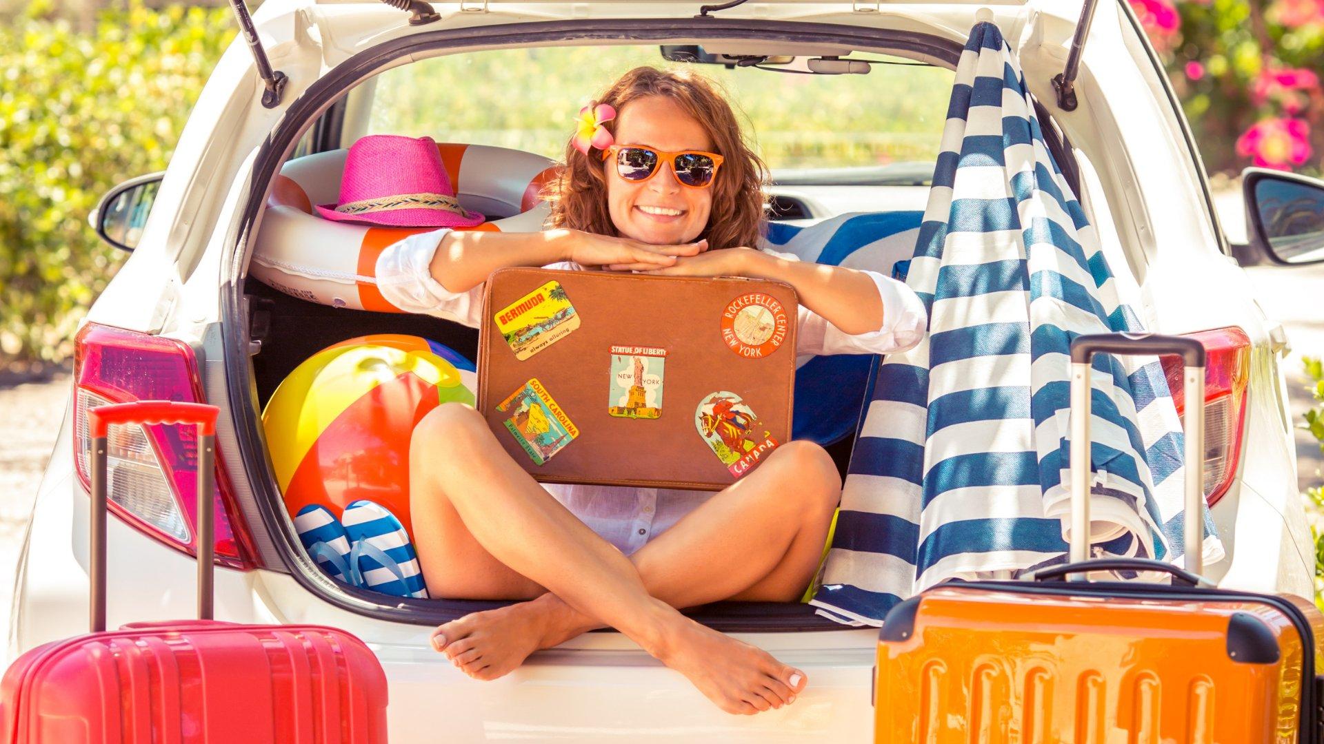 Garota sorrindo com óculos escuros no porta-malas de um carro com bagagens, bolas e boias de praia