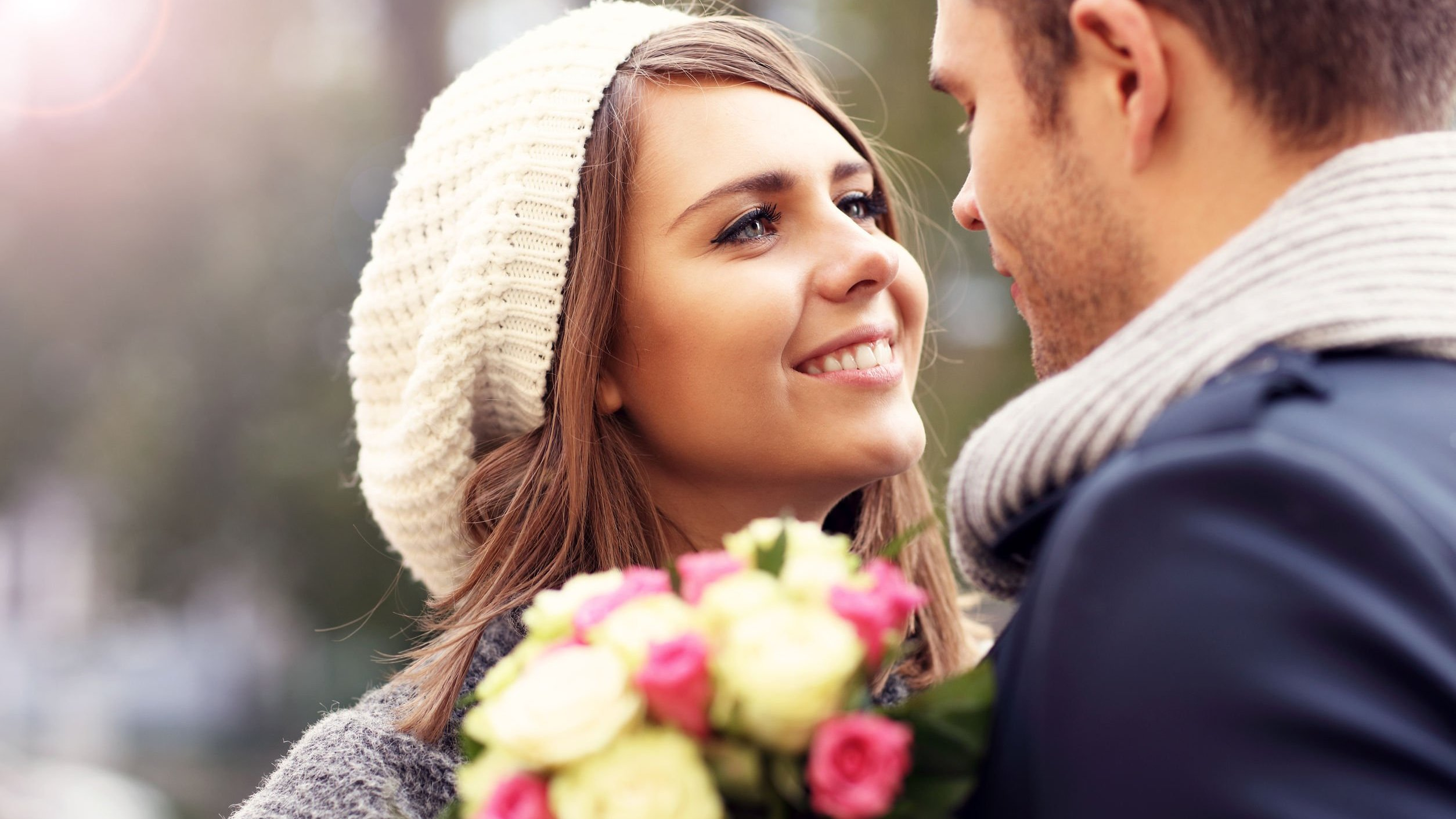 Mulher olhando para homem e sorrindo, segurando flores.