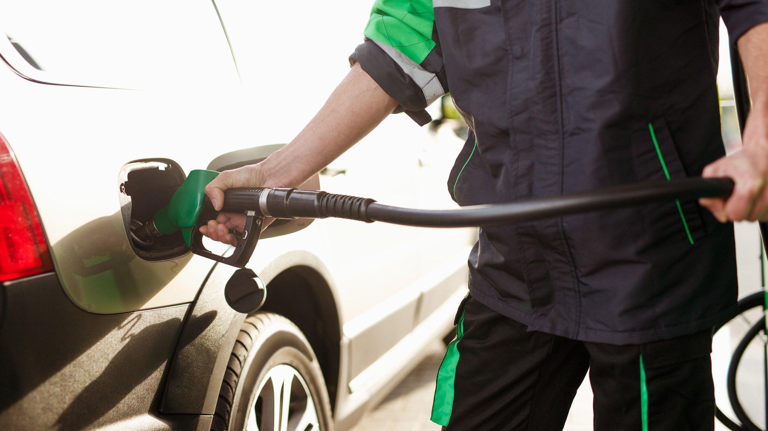 Frentista de posto de gasolina, colocando gasolina em carro.