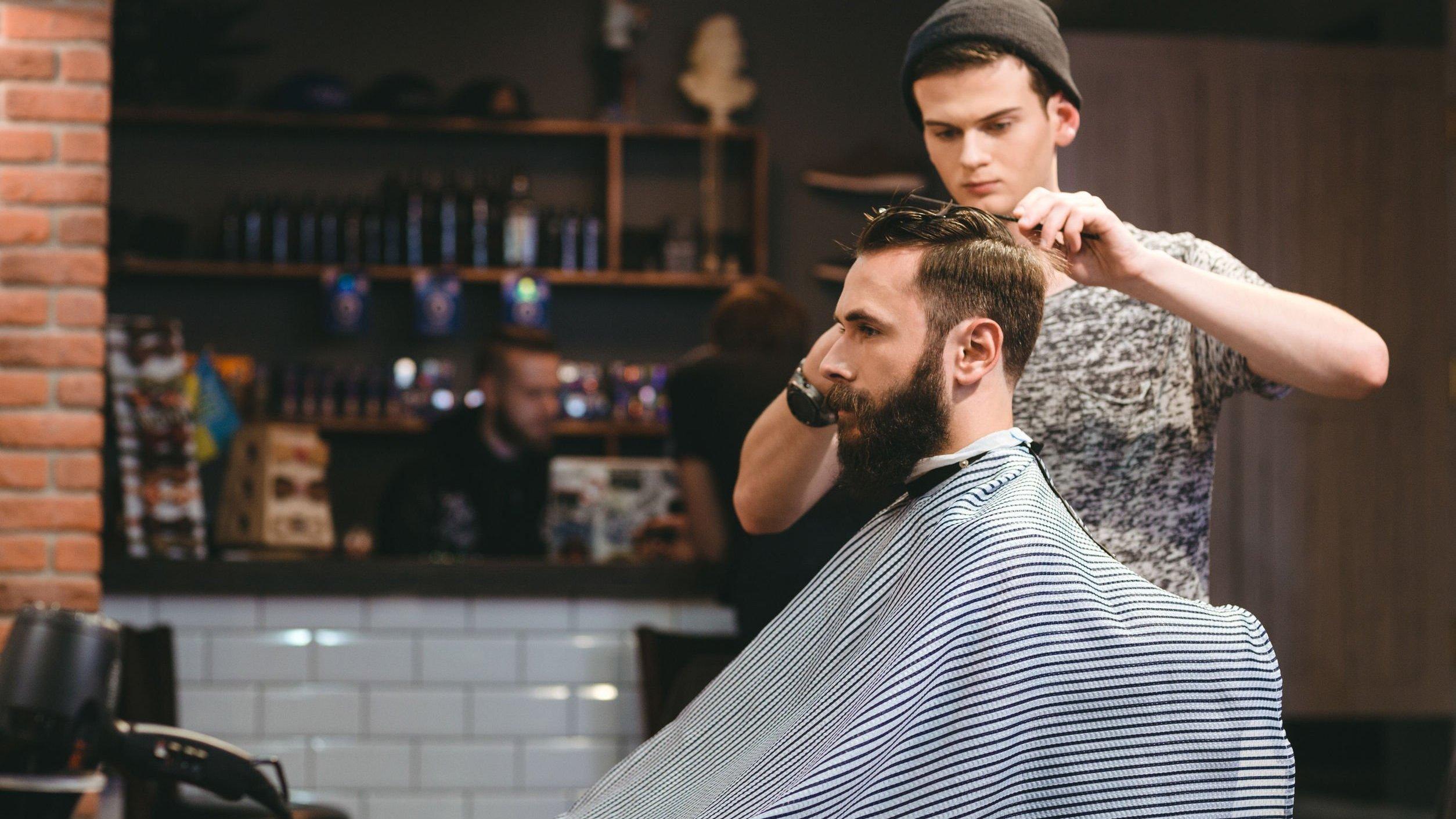 Cabeleireiro cortando cabelo de cliente sentado em cadeira.