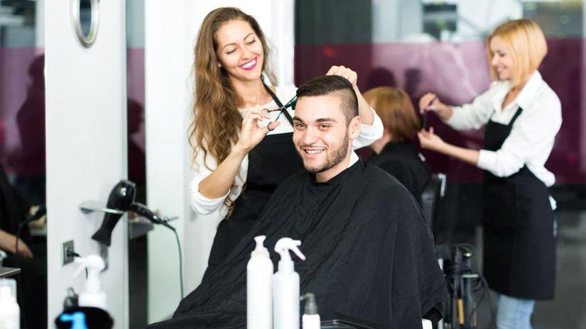 Cabeleireira cortando o cabelo de um homem no estúdio de cabeleireiro