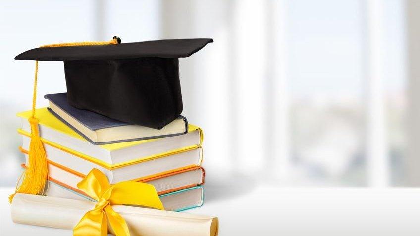 Livros empilhados, diploma e capelo