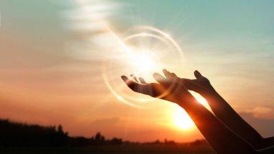 Mãos de mulher rezando com pôr do sol no fundo