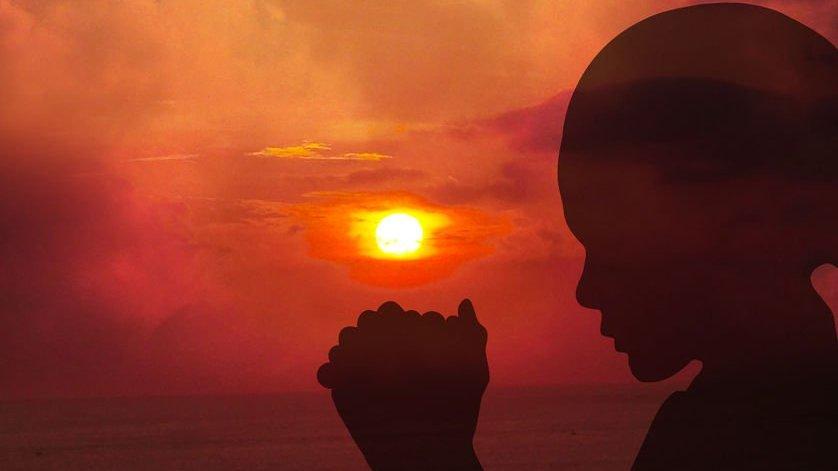 Sombra de uma mulher rezando ao pôr do sol