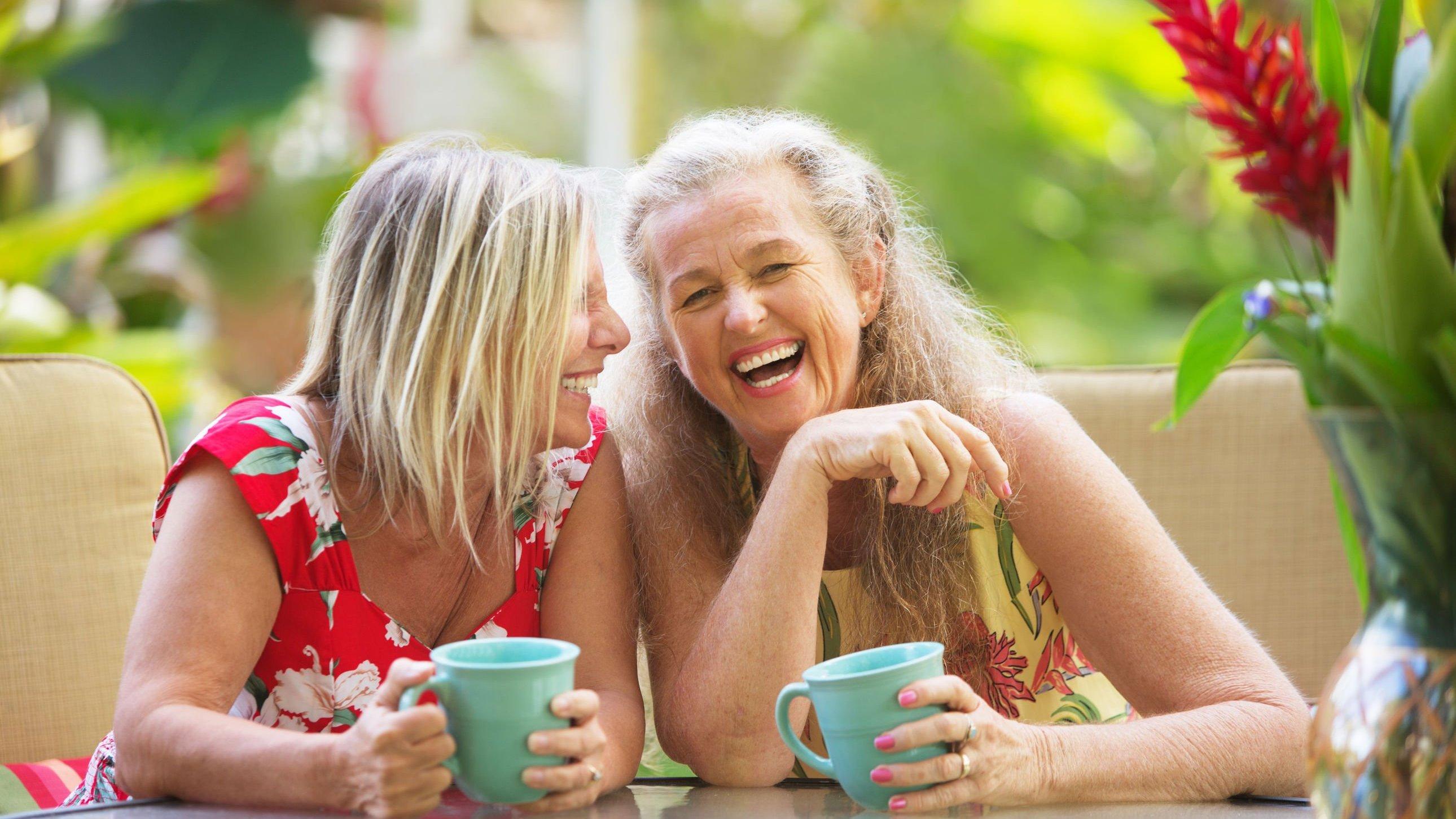 Duas mulheres seguram canecas e dão risadas. Ambas estão sentadas.