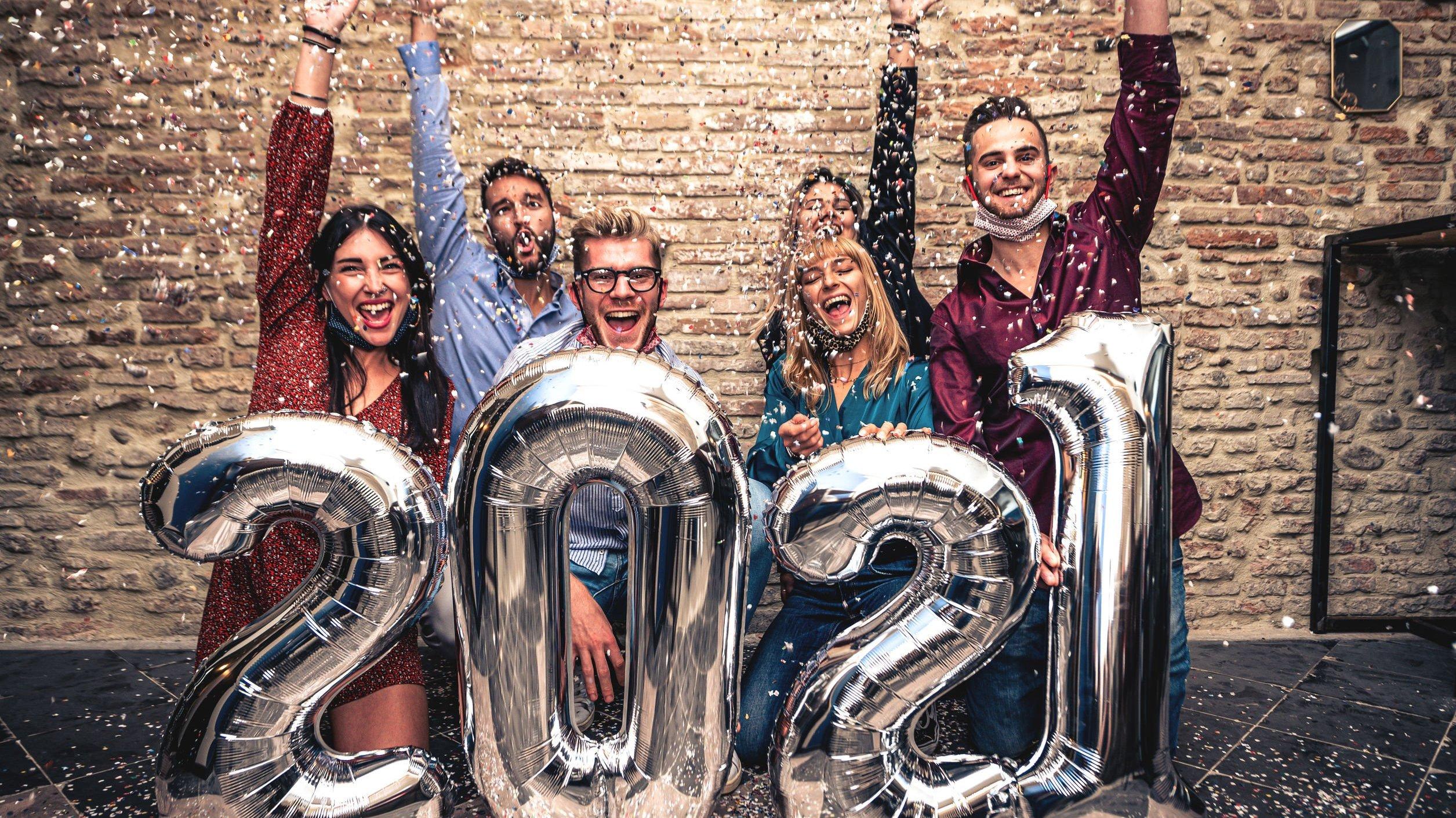 Grupo de amigos comemora o ano novo em frente a balões de número 2021.