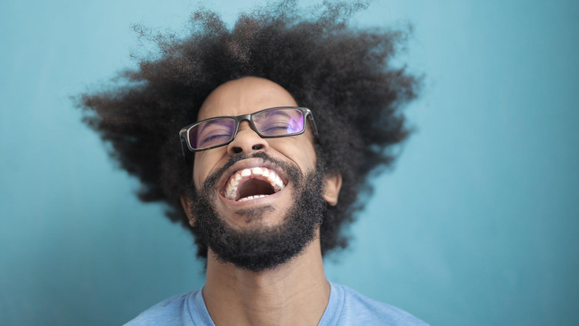Homem negro usando óculos sorrindo largo