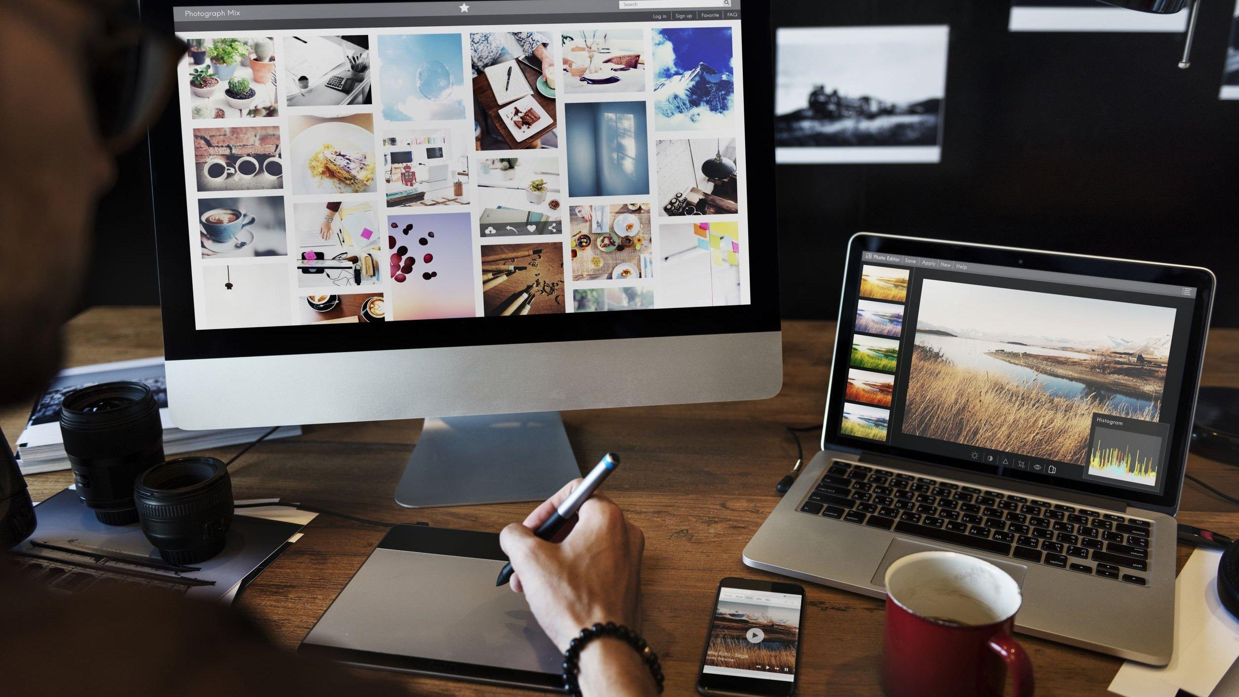 Ilustrador sentado em frente de dois computadores