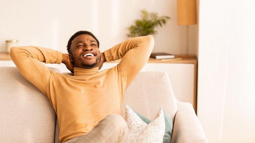 Homem sentado no sofá, sorrindo