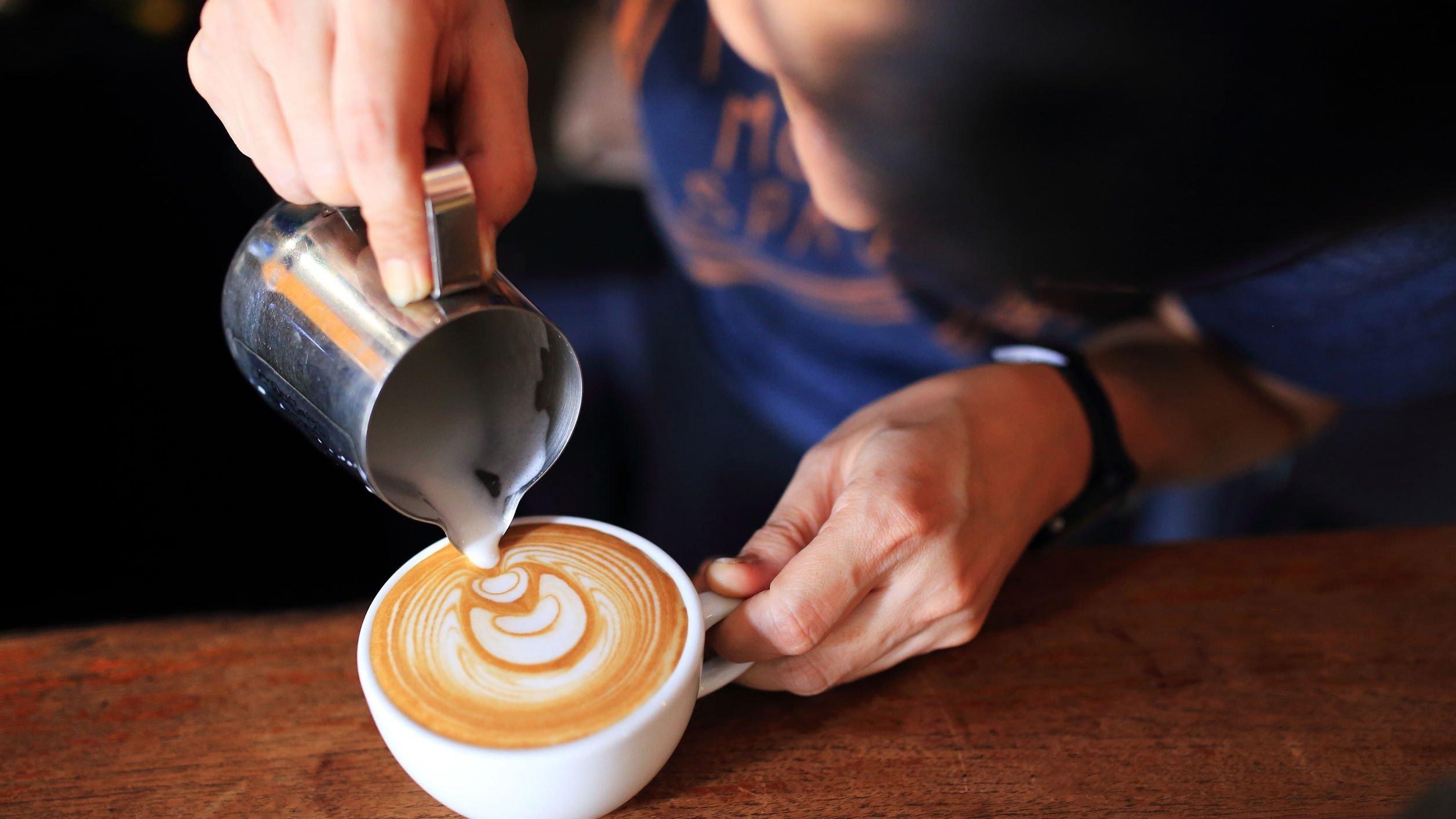 Homem colocando leite em xícara.