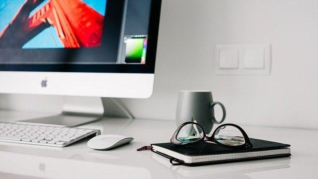 Mesa com computador, caderno e óculos em cima