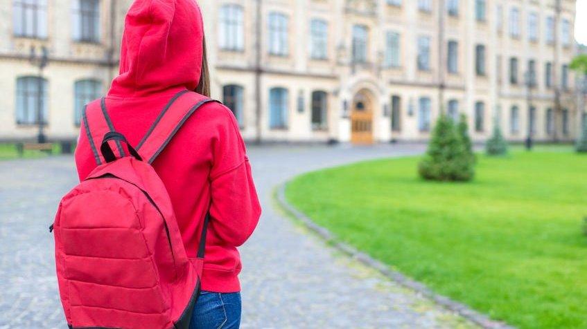 Pessoa com mochila nas costas entrando em faculdade