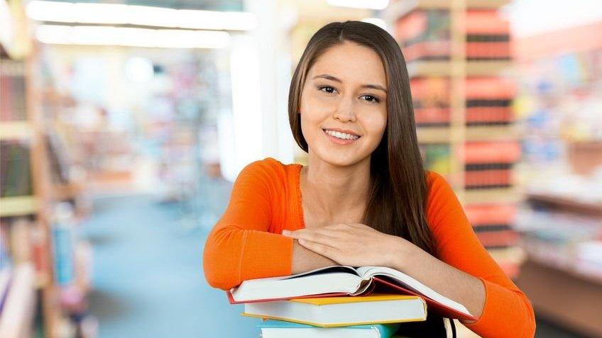 Menina apoiada em livros