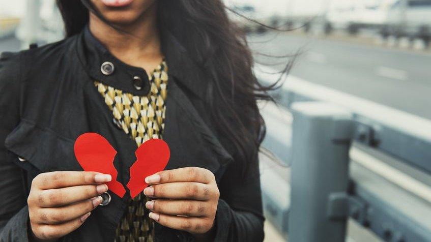 Mulher segurando coração partido