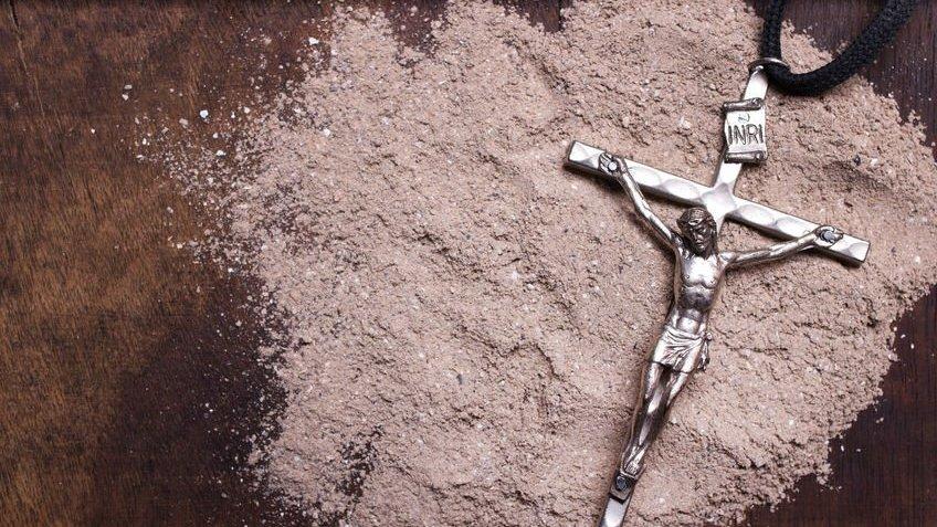 Pingente de Jesus Cristo sobre areia