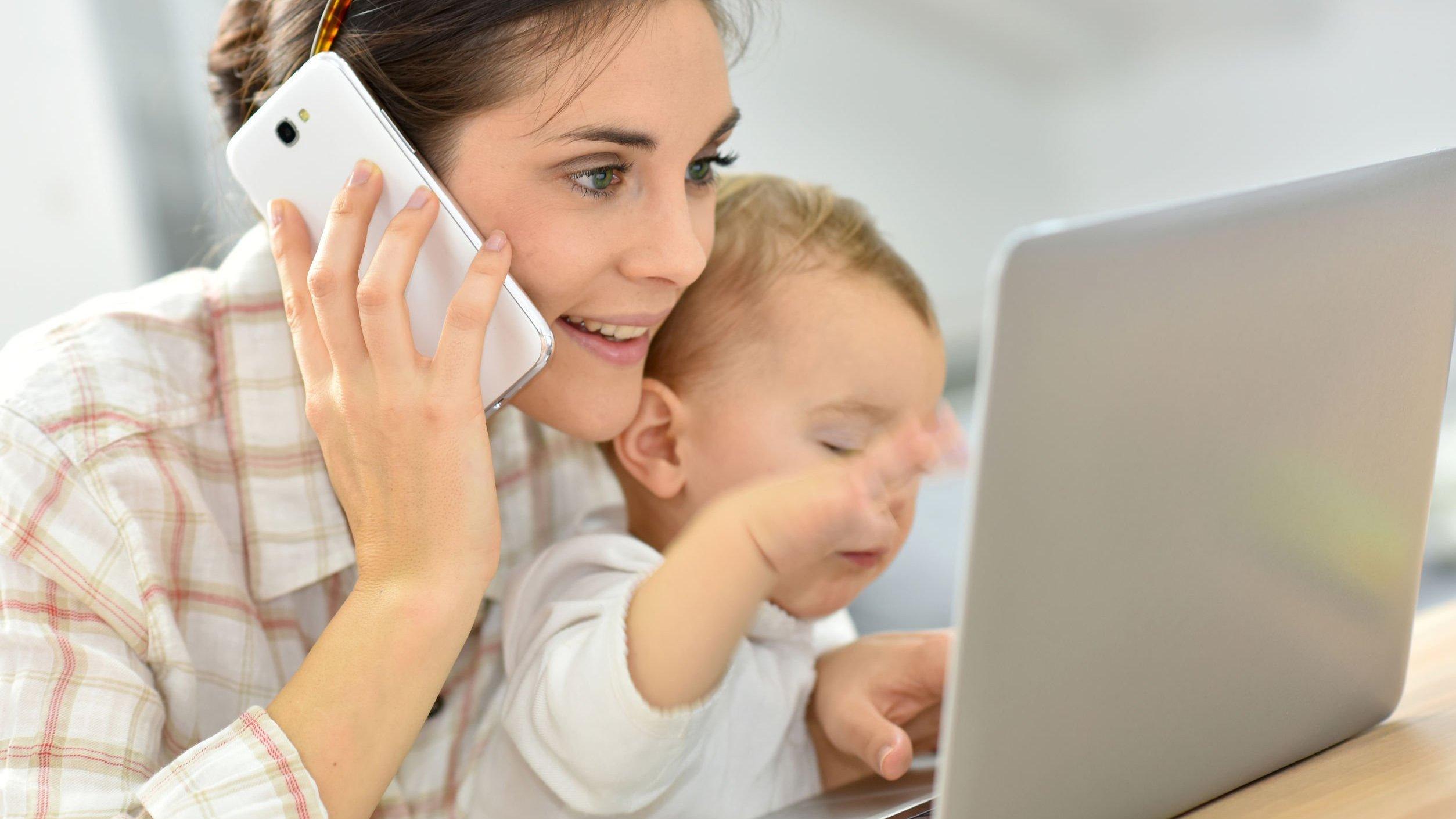 Mãe segurando filho, falando no celular em frente a notebook.